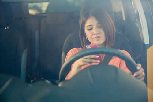 [cml_media_alt id='3141']Woman distracted on her phone while driving, placing a pedestrian at risk[/cml_media_alt]