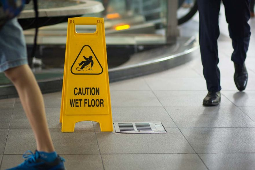 A business trying to prevent slip, trip and fall accidents with a caution sign.