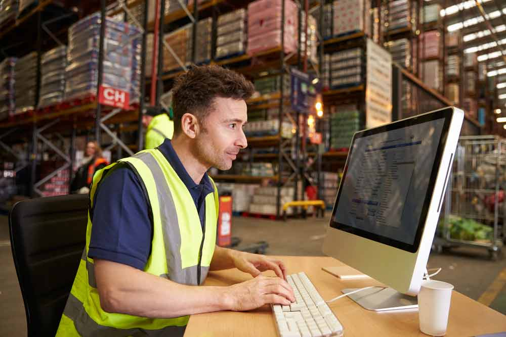 Man at a desk in a warehouse due to light duty work restrictions